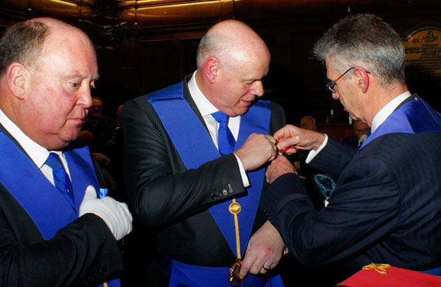 The PGM receiving his 2021 Jewel from W. Bro. Sir Paul Williams.